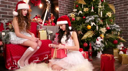 enfeite de natal : Two girls near Christmas tree in New Year, preparing gifts for family, Help Santa Claus lay out business cards for Christmas boxes, Celebrate Winter Holiday, carnival costume and Santa hat Stock Footage