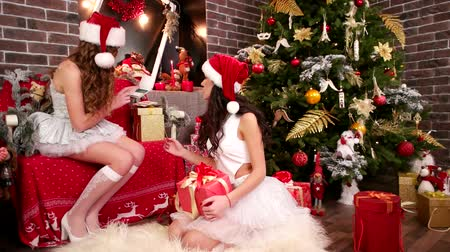 fur headphones : Sexy girls in Santa Claus hats near Christmas tree, Two friends wrapping festive boxes, On New Years Eve, sisters make presents, Merry Beauties prepare for Christmas, carnival costume and Santa hat