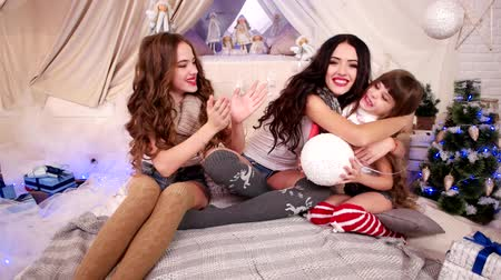 ámulat : On New Years Eve three young girls dream, Three sisters celebrate winter holidays in cozy atmosphere, New Years mood of beautiful girls, On Christmas Eve, happy family dressed up warm scarves, socks