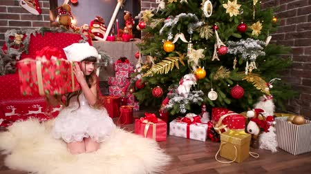 elf : New Years gifts under Christmas tree for younger sister, presents from Santa Claus for daughter, close-up of little girl with Christmas gifts, happy winter holidays, plays with gifts in the house