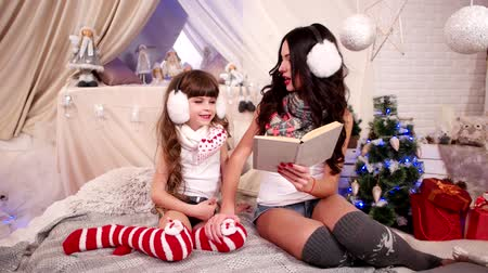 fur headphones : reading Christmas tale to little, happy family near Christmas tree with New Years gifts watching book, Girls are enjoying Winter Holidays, cozy atmosphere, dressed up warm scarves Stock Footage