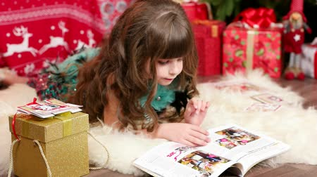 fur headphones : little girl with long hair reads magazine and dreams of miracle for Christmas, Daughter is waiting for Winter Holidays, Gifts and postcard for her sister for New Year, Reads lying on the floor