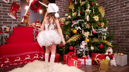 elfo : little girl found gifts under Christmas tree, daughter in Elf Santas costume chooses surprise for New Year, Christmas tree with gifts for little fairy, winter holiday, assistant of Santa Claus