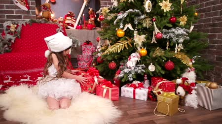 elfo : Little Elf Santa in New Years room, Christmas tree, gifts for her beloved daughter, little girl was presented with many bright gifts, girl in New Years costume snowflakes, plays with gifts in house