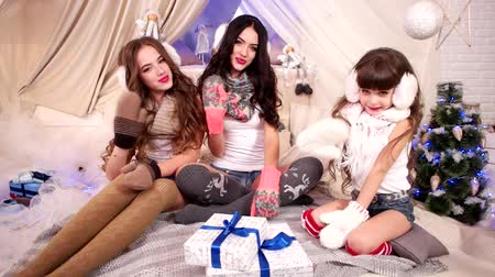 fur headphones : Happy young girls in warm earphone and scarf blowing kiss close-up, Family in cozy New Years room near Christmas tree, Three sisters celebrating winter holidays, Christmas gifts for beautiful girls,