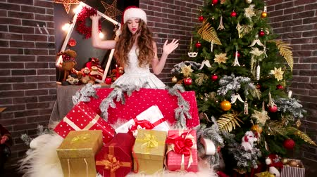 святки : Happy girl found gifts, Young girl in room with holiday boxes, Prepares gifts for Christmas, On New Years Eve, surprise from Santa Claus near Christmas tree, Assistant Santa Claus puts presents