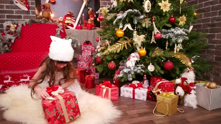 elves : Great Christmas gift for little girl, close-up of New Years room and Christmas tree, curious Santa Claus helper, Happy winter holiday for little beauty, plays with gifts in house, carnival costume