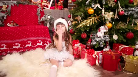 elfo : Girl in Snow costume blowing kiss, close-up, New Years greetings from little Santa Claus helper, Daughter playing in Christmas room, Winter Vacations for little gir, plays with gifts in house