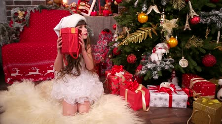 csőd : girl in New Years costume near Christmas tree with New Years surprise, Happy Christmas Vacation for younger sister, gift from Santa Claus for her daughter, plays with gifts in house, winter holiday
