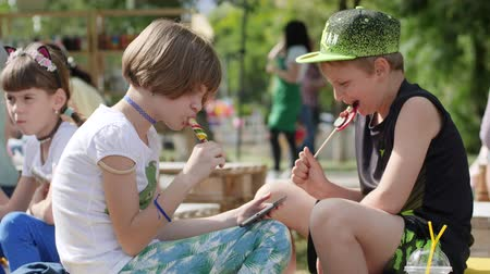 delikanlı : Kherson, Ukraine - 27 May 2017: City Festival boy and girl eating caramel candy in park, kids with colourful candies and tablet digital in hand, children eat lollipop in garden, slow motion Stok Video
