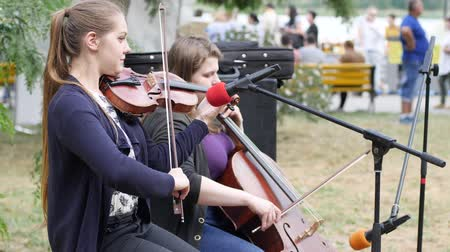 protrude : Kherson, Ukraine - 27 May 2017: City Festival artists perform musical composition on violoncello and violin for passersby, girls play on musical instruments outdoors, street musicians earn money, Stock Footage