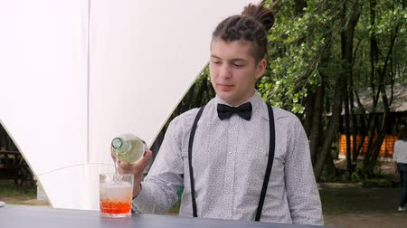 шейкер : bartender makes mixed drink on background nature, bar worker topped up rom into glass with ice cubes, barman preparing alcoholic cocktail, male tapster on bar counter, slow motion