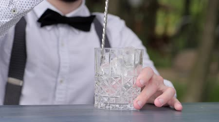доля : glass with ice on bar counter, barman stirring ice bar spoon close-up, bartender makes cooling beverage to fresh air, cocktail jar in hands of guy barman, barkeeper prepare an order, Cocktail party Стоковые видеозаписи