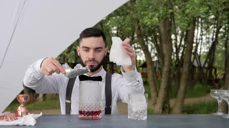 доля : bartender adds ice to glass of liquor in bar counter, barman put ice into glass with alcohol and holding napkin, bar worker prepares cooling cocktail on nature, barkeeper makes an alcoholic drink,