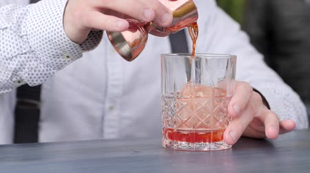 доля : barman pours juice into glass with ice on bar counter, barkeeper prepares cooling cocktail, bar worker adds liquor in ice close-up, barkeeper makes cold beverage to fresh air, Cocktail party Стоковые видеозаписи