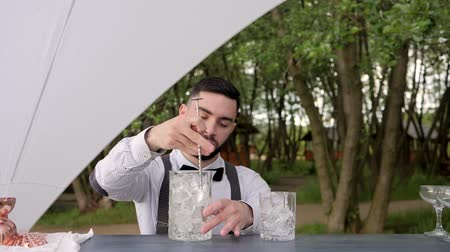 доля : barkeeper stirring ice cubes bar spoon on nature, glass with ice on bar counter, bartender makes cooling beverage to fresh air, cocktail jar in hands guy barman, barman prepare an order, event Service