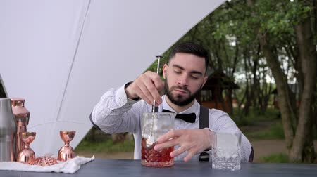 доля : barkeeper on bar counter stirring alcohol with ice in glass, barman makes alcoholic drink outdoors, bartender prepares cooling cocktail from liquor with ice, bar worker makes cocktail, Summer cafe Стоковые видеозаписи