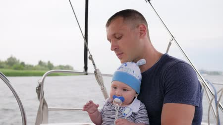 уик энд : parent with child outdoors, daddy holding his son on yacht, father and little boy with pacifier in his mouth, family rest on river, lucky small child and dad during summer holidays