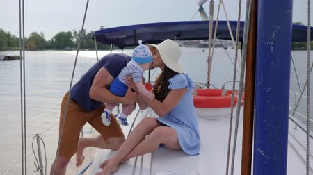 три человека : family trip at loch in pleasure boat, travel young parents with little boy on river, holiday of happy couple with baby at sailing yacht in sea, portrait of happy family resting in boat on lake, Стоковые видеозаписи
