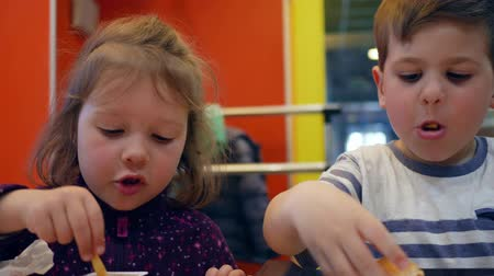greedily : Lovely brother and sister have snack with crispy potatoes in restaurant, Tasty French fries with sauce for little girl and boy, Male child chews hamburger, Active and fun kids play with meal Stock Footage