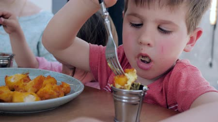 greedily : Little twins eats fork fried chicken nuggets with sauce, Boy and girl are having an appetizing dinner in restaurant, Lovely kids eat at fast food cafe, Beautiful brother and sister make snack eating