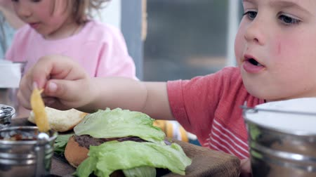 greedily : Hamburger with leaf of lettuce and French fries with sauce for brother and sister for snack, Two funny little kids eat French fries with sauce in fast food cafe, Family is eating harmfully food, Stock Footage