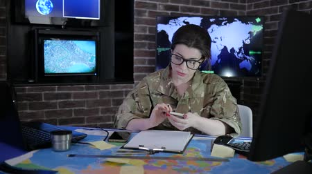 safeness : woman portrait soldier in glasses and uniform, working with laptop and mobile phone, in computer center, safety system tracking terrorists, on background multiple displays and world map
