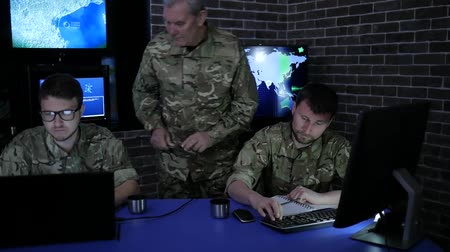 safeness : War center, wise general beside from two soldier, monitoring room, working process at briefing, discussing battle strategy, background group people at camouflage uniform near on-screen monitors