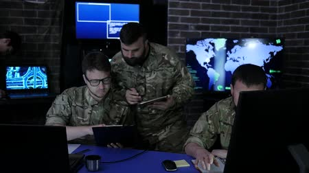 superior : warriors in uniform, War center, working in digital tablet, sketch pad and laptop, in military base, discussing assault, security service and tracking terrorists, on background display screens