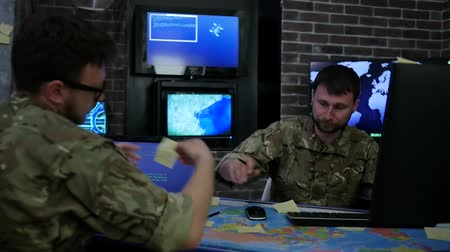 safeness : Two serious soldiers in uniform, War center, monitoring room, working for laptop, search safety system, briefing discussing battle strategy, on background multiple displays and world map Stock Footage