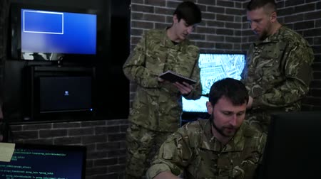 cuidado : Two professional soldier in uniform, in military base, working for laptop, system tracking terrorists, briefing, on background multiple displays and group specialist discussing battle strategy