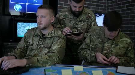 safeness : soldiers in uniform, working in digital tablet, notebook and laptop, in military base, discussing assault, War center, security service and tracking terrorists, on background display screens