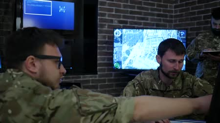 командир : soldiers mans in uniform, in military headquarters, IT war working process, warning dangers, working on computers showing various information, on background Multiple Displays Стоковые видеозаписи