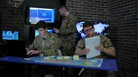safeness : soldier in camouflage uniform, view maps and working in laptoop, Military headquarters, briefing in monitoring room, discussing assault, security service and tracking terrorists, on background display screens Stock Footage