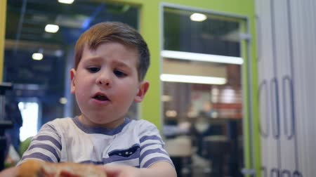 unhealthy eating : Harmful food for beautiful kid in childrens cafe, Fast food school snack for son in dining room, Cute hungry boy quenches hunger with harmful meal in street cafe, Little boy eating at table burger, Stock Footage