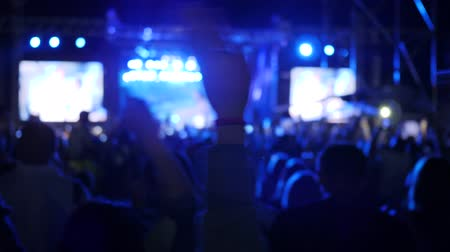 scena : silhouette of crowd illuminated by colored fire of stage, fans waving hands at concert party, excited audience rocking hands on music festival, arms raised of people in bright lights on rock festival,