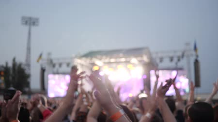concert crowd : rock concert, fans applauded arms on concert, many people clap their hands, audience at outdoors, lit scene by colourful illumination during night festival, many lights on stage, slow motion Stock Footage