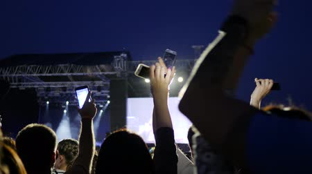 alfândega : phones in raised hands crowds on background stage lights, people on concert waving hand with mobiles, public with mobile telephone on rock festival, illuminated scene on party