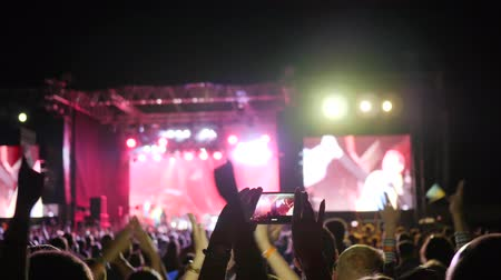 película de filme : people jumps and clap at concert, fan person records video and takes pictures on smart phone at concert party, mobile phone in hand makes photo of illuminated stage at rock festival, Stock Footage