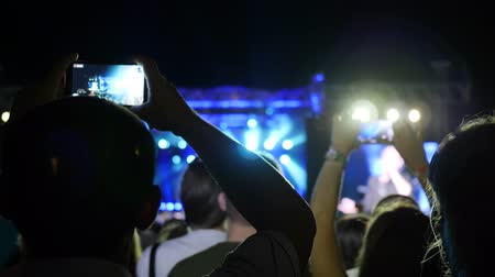 alfândega : mobile in hand fan, people on concert hold in hand phones, audience at rock concert with android, fans makes photo on telephone, illuminated scene on party, many lights on stage rock festival