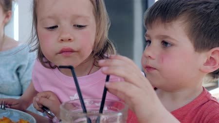 greedily : Kids drink juice through straw, together from one glass sitting at table in cozy street cafe, Beautiful brother and sister make snack in restaurant, Two funny little children are having dinner in cafe Stock Footage
