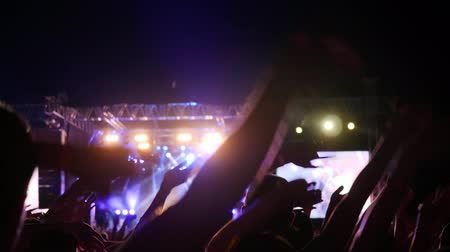 жить : fans waving hands at concert party, excited audience rocking hands on music festival, arms raised of people in bright lights on rock festival, crowd illuminated by colorific fire during concert,
