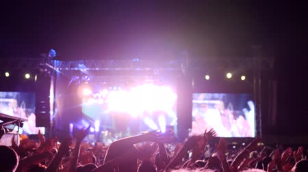 авиашоу : crowd of fans waving arms and hold phone with digital displays at rock concert, many arms raised of people in bright lights of stage, excited audience rocking hands on music festival,