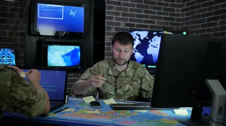 safeness : serious officer men in camouflage uniform in system control center, working for laptop, briefing discussing battle strategy, on background multiple displays and world map, Military headquarters
