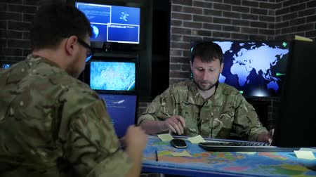 штаб квартира : pro officer men in camouflage uniform, in system control center, working for laptop, briefing military IT technicians, discussing battle strategy, on background multiple displays and world map Стоковые видеозаписи