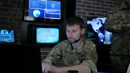 safeness : portrait warrior male in shape, in monitoring room, military control and security service, safety system tracking terrorists, on background Workstation, beside monitor and employees Stock Footage