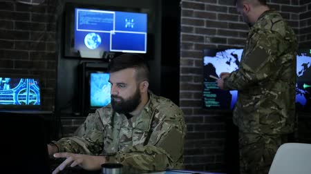 odeslání : portrait soldier man in uniform, in military headquarters, IT war working process, warning dangers, working on computers showing various information, on background Multiple Displays and team Dostupné videozáznamy