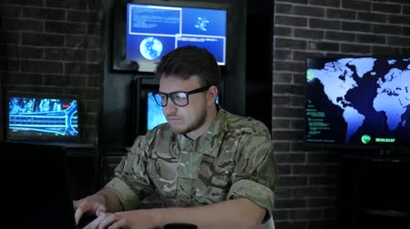 safeness : portrait smiling soldier in uniform, in headquarters, Cyber Terrorism and control safety system, briefing military group, on background computer and accomplished IT specialists Stock Footage