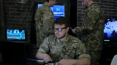 safeness : portrait serious soldier in uniform, in military headquarters, cyberterrorism and searches safety system, briefing military IT technicians, on background multiple displays and specialist Stock Footage