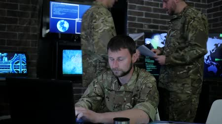 safeness : portrait proficient soldier, in military base, working for laptop, system tracking terrorists, briefing, on background multiple displays and group specialist discussing battle strategy